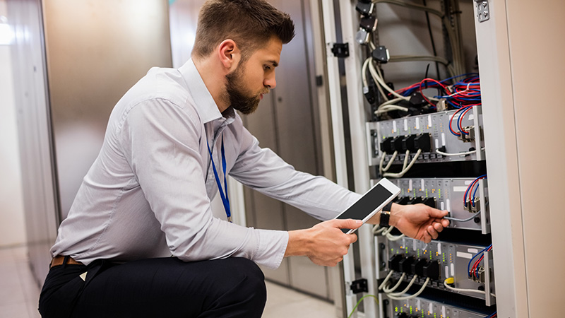 technician checking wires on server